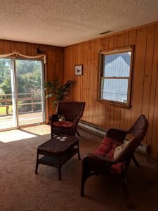 living room seating area, sliding glass door, and wood panelling