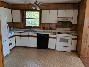 full kitchen with wood paneled walls, white cabinets, and tile floor