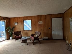 completed living room with wood paneling and carpet
