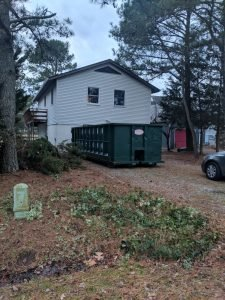 driveway with a dumpster next to the house