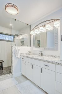 large white modern bathroom with granite countertop and tiled shower