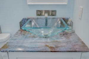 modern clear sink bowl with dark marbled countertop