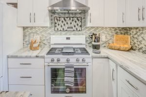 kitchen oven and stove with granite countertop and tiled backsplash