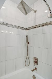 white tiled modern shower with marble detailing