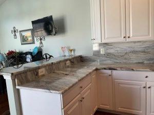 kitchen with granite breakfast bar, countertop and backsplash