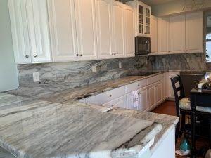 kitchen with granite breakfast bar, full backsplash and countertop
